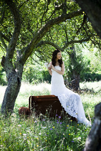 Bride in white wedding dress posing at the meadow
