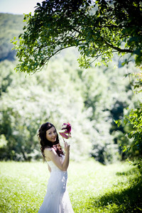 Bride in white wedding dress with mask posing at the meadow