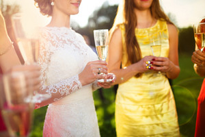 Bride with four happy bridesmaids toasting at the wedding reception outside
