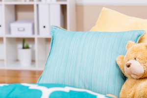 Bright living room interior with a teddy bear and aqua sofa pillows