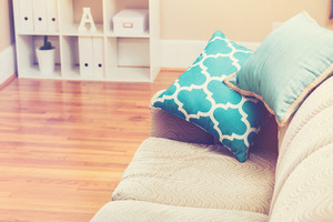 Bright living room interior with turquoise sofa pillows