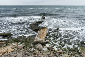Broken concrete slabs on the rocky shore among the rocks and waves