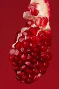 Broken pomegranate segment isolated on red background