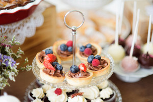Brown wooden table with fresh fruit tarts with chocolate cream and cupcakes on cakestand. Studio shot.