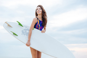 Brunette girl dressed in swimsuit standing at the ocean ready to surf