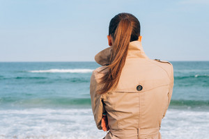 Brunette in beige coat looks on the sea, the view from the back