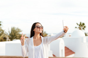 Brunette woman in white clothes and sunglases which making selfie on phone