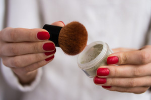 brush and powder in female hands with red nails