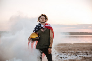 Brutal man wearing usa flag cape posing in white smoke and holding golden helmet outdoors