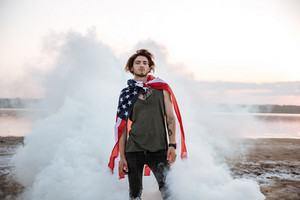 Brutal man wearing usa flag cape posing in white smoke outdoors
