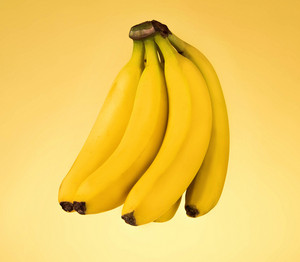 Bunch of fresh bananas isolated on yellow background