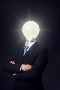 Business consept with a man with a lighting bulb as head. Power or green energy concept. Smart man or a bright idea.