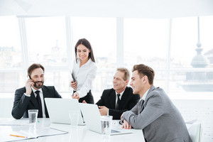 Business group sitting by the table near the window in conference room