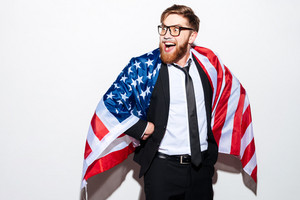 Business man in glasses and suit wrapped in USA flag with open mouth looking aside. Isolated gray background