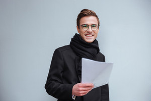 Business man in glasses and warm clothes looking at documents and standing near the wall