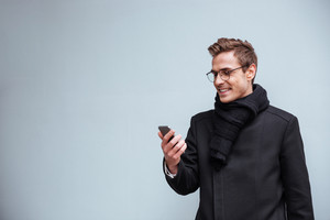 Business man in glasses and warm clothes looking at phone. isolated