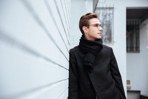 Business man in glasses and warm clothes standing near the wall of house and looking away