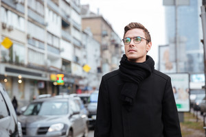 Business man in glasses and warm clothes walking on the street and looking aside