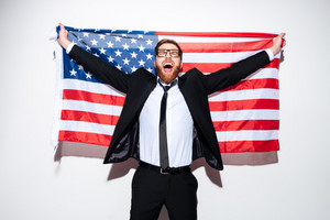 Business man in suit and glasses holding USA flag from his back with open mouth. Isolated gray background
