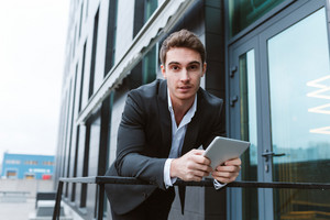 Business man in suit standing with laptop computer near the office and looking at camera