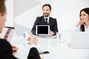 Business man showing blank tablet computer screen and sitting by the table with Colleagues