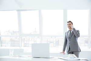 Business man standing near the window and talking at phone in conference room