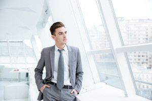 Business man standing near the window in office with arms in pockets and looking away