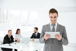 Business man using tablet computer in office with colleagues on background
