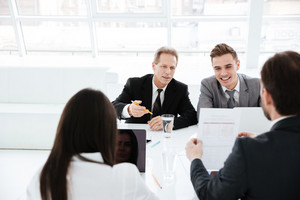 Business people sit by the table in conference room
