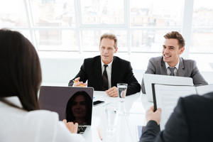 Business people sitting by the table and interacting at a meeting in conference room