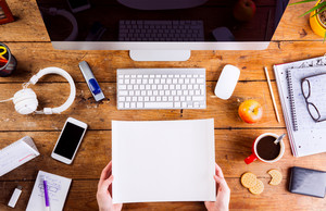 Business person working at office desk. Holding a sheet of paper. Smart phone on the table. Copy space. Flat lay.