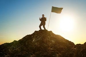 business, success, leadership, achievement and people concept - silhouette of businessman with flag on mountain top over sky and sun light background