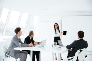 Business team sitting by the table in office on session and woman standing near the board