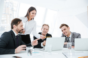 Business team sitting by the table with laptops in office