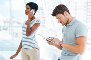 Business woman and man working together in conference room with smartphone