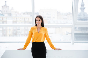Business woman in orange shirt standing near the window in office and looking at camera