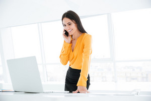 Business woman in orange shirt talking at phone near the table and looking at laptop