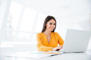 Business woman in orange shirt using laptop computer and sitting by the table in office