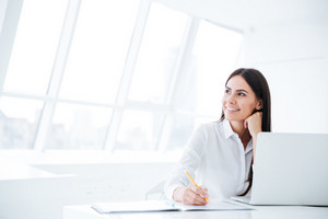 Business woman sitting by the table with laptop and looking away in office