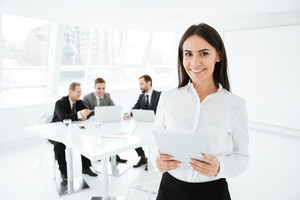 Business woman standing in office with business group on background and holding documents