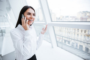 Business woman talking at phone and standing near the window