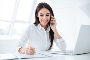 Business woman talking at phone and writing something in documents by the table with laptop