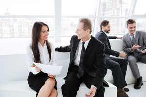 Business woman talking with business partner and sitting on sofa in office with Colleagues on background