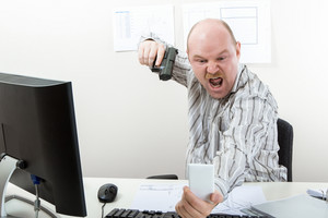 Businessman Aiming Gun On Mobile Phone At Desk