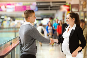 Businessman and businesswomen having a meeting in shopping mall. Woman is pregnant.
