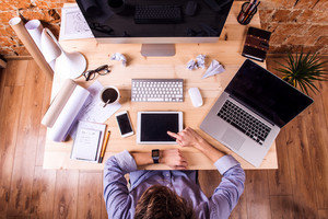 Businessman at the desk, wearing smart watch, working on tablet.  Computer, smart phone, notebook and various office supplies around the workplace.
