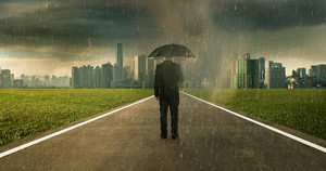 Businessman below storm rain with umbrella , risk and crisis concept .