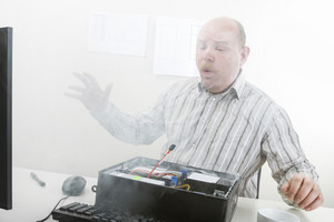 Businessman Blowing Smoke Emerging From Computer Chassis