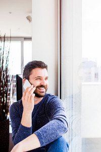 Businessman in blue long sleeved t-shirt working from home, holding smartphone, making phone call