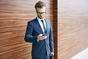Businessman in suit and eyeglasses using cellphone